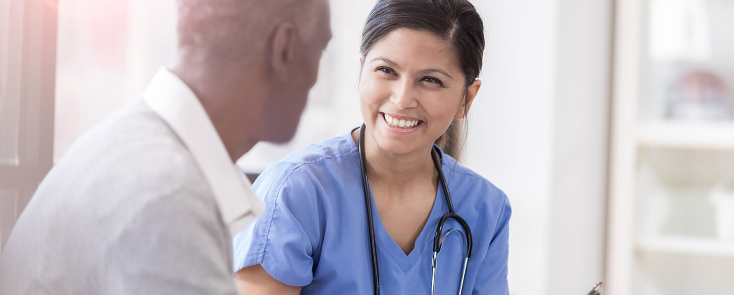 Female nurse talking to a male patient